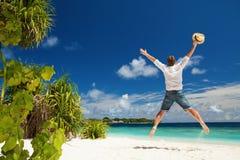 Hombre feliz que salta en la playa tropical Fotos de archivo libres de regalías