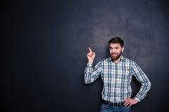 Hombre feliz que señala el finger en el copyspace Fotografía de archivo