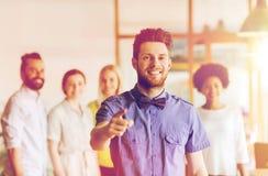 Hombre feliz que señala el finger en usted sobre el equipo de la oficina Fotografía de archivo