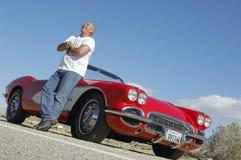 Hombre feliz que se coloca al lado del coche clásico en el camino foto de archivo