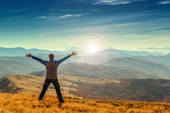 Hombre feliz que se coloca en el top de la montaña con los brazos aumentados Imagen de archivo libre de regalías