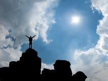 Hombre feliz que se coloca en el top de la montaña Imágenes de archivo libres de regalías