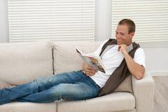 Hombre feliz que se relaja en el sofá Imágenes de archivo libres de regalías