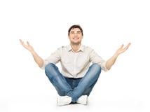 Hombre feliz que se sienta con las manos aumentadas para arriba Foto de archivo