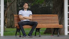 Hombre feliz que se sienta en banco de parque imágenes de archivo libres de regalías