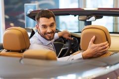 Hombre feliz que se sienta en coche en el salón del automóvil o el salón fotos de archivo