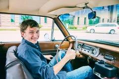 Hombre feliz que se sienta en coche y que muestra el pulgar para arriba Fotografía de archivo libre de regalías