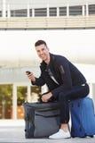 Hombre feliz que se sienta en el equipaje con esperar del teléfono móvil Fotografía de archivo