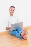 Hombre feliz que se sienta en el piso usando el ordenador portátil Foto de archivo