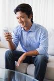 Hombre feliz que se sienta en el sofá que manda un SMS en el teléfono foto de archivo