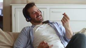 Hombre feliz que se sienta en los auriculares que llevan del sofá que escuchan la música almacen de video