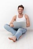 Hombre feliz que se sienta en suelo con la computadora portátil Fotos de archivo