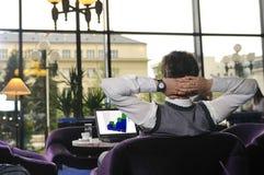 Hombre feliz que se sienta y que trabaja en la computadora portátil Imagen de archivo libre de regalías