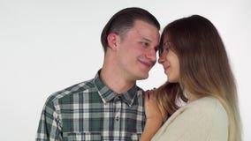 Hombre feliz que sonríe cuando su novia hermosa que lo besa en la mejilla metrajes