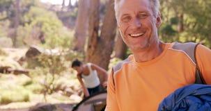 Hombre feliz que sonríe en el sitio para acampar almacen de metraje de vídeo