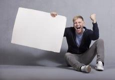 Hombre feliz que sostiene el panel vacío blanco. Foto de archivo
