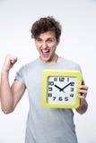 Hombre feliz que sostiene el reloj con los brazos aumentado Fotografía de archivo