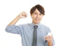 Hombre feliz que sostiene el teléfono elegante Imagen de archivo