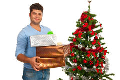 Hombre feliz que sostiene los regalos de la Navidad Imagenes de archivo