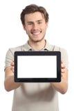 Hombre feliz que sostiene y que muestra una pantalla horizontal en blanco de la tableta Foto de archivo