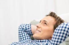 Hombre feliz que sueña despierto en el sofá Imagen de archivo libre de regalías
