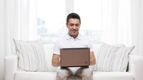 Hombre feliz que trabaja con el ordenador portátil en casa metrajes