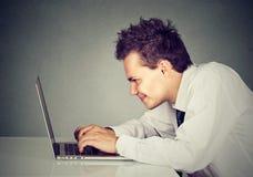 Hombre feliz que trabaja en el ordenador portátil Imagen de archivo