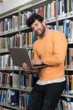 Hombre feliz que trabaja en la computadora portátil Imagen de archivo