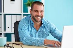 Hombre feliz que trabaja en oficina Fotos de archivo