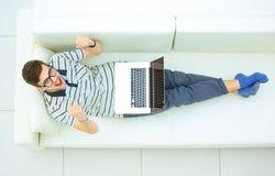 Hombre feliz que trabaja en su ordenador portátil en el sofá en casa imágenes de archivo libres de regalías