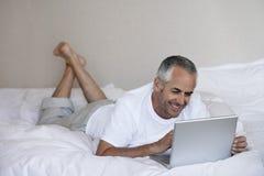 Hombre feliz que usa el ordenador portátil mientras que miente en cama Foto de archivo