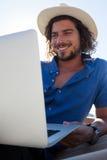 Hombre feliz que usa el ordenador portátil mientras que se relaja en la hamaca en la playa Fotografía de archivo