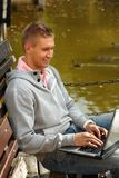 Hombre feliz que usa la computadora portátil por el lago Imágenes de archivo libres de regalías