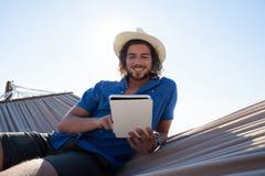 Hombre feliz que usa la tableta digital en la hamaca en la playa Fotografía de archivo libre de regalías