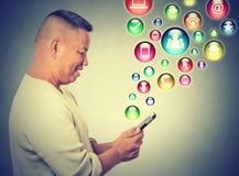 Hombre feliz que usa mandar un SMS en iconos sociales del uso del smartphone los medios que vuelan para arriba Imagenes de archivo