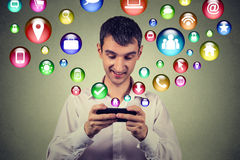 Hombre feliz que usa mandar un SMS en iconos sociales del uso del smartphone los medios que vuelan para arriba Fotografía de archivo libre de regalías
