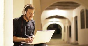 Hombre feliz usando un ordenador portátil con los auriculares en la noche metrajes