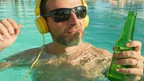 Hombre feliz y atractivo joven que escucha la música con las auriculares en el goce de consumición tropical de la cerveza de la p metrajes