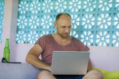 Hombre feliz y confiado joven del backpacker que trabaja con el ordenador portátil al aire libre relajado como empresario indepen imágenes de archivo libres de regalías