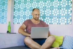 Hombre feliz y confiado joven del backpacker que trabaja con el ordenador portátil al aire libre relajado como empresario indepen foto de archivo