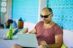Hombre feliz y confiado joven del backpacker que trabaja con el ordenador portátil al aire libre relajado como empresario indepen imagen de archivo