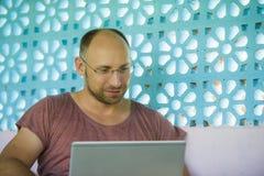 Hombre feliz y confiado joven del backpacker que trabaja con el ordenador portátil al aire libre relajado como empresario indepen fotos de archivo libres de regalías
