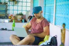 Hombre feliz y confiado joven del backpacker que trabaja con el ordenador portátil al aire libre relajado como empresario indepen fotografía de archivo