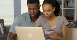 Hombre feliz y mujer afroamericanos que hacen la compra en línea con la tarjeta de crédito Foto de archivo