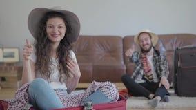 Hombre feliz y mujer del retrato que se sientan en el piso antes de viaje en casa Mujer linda que se sienta en la maleta y la a almacen de video