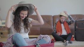 Hombre feliz y mujer del retrato que se sientan en el piso que embala una maleta antes de viaje en casa La esposa que se sienta e almacen de video