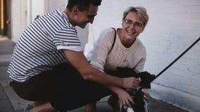 Hombre feliz y mujer hispánicos jovenes de Europea que acaricia un pequeño perro y que sonríe alegre en calle de la tarde del ver almacen de metraje de vídeo