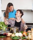 Hombre feliz y mujer que cocinan la sopa Fotos de archivo libres de regalías