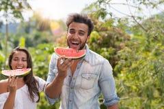 Hombre feliz y mujer que comen la sandía junto sobre la tenencia tropical hermosa de Forest Landscape Cheerful Couple Laugh Fotografía de archivo