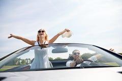 Hombre feliz y mujer que conducen en coche del cabriolé imagen de archivo